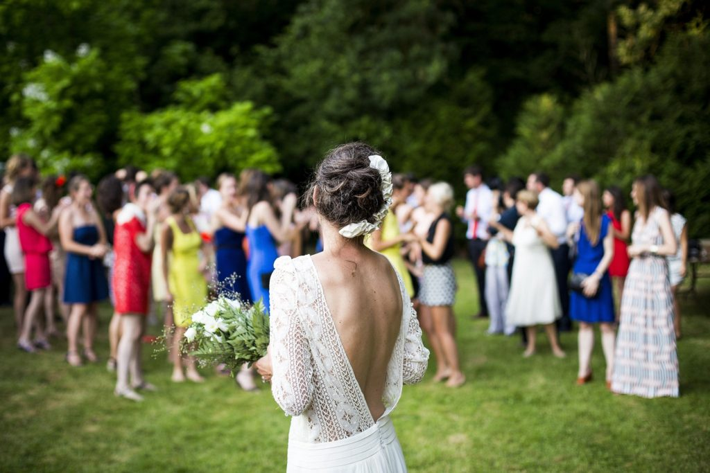 A woman prepares to throw the bridal bouquet at an outdoor event venue.